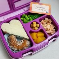 09.18.17    Egg salad sandwich cut into a heart shape; edamame; sliced cucumber; salmon; diced peaches; chickpeas; 1/2 an apple cider doughnut